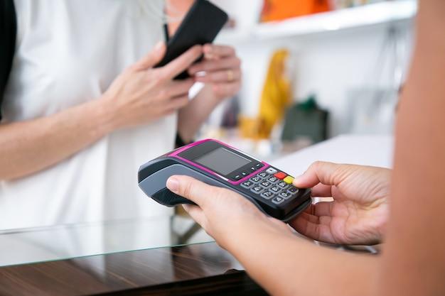 Kassier die het betalingsproces uitvoert, knoppen op de betaalautomaat indrukken terwijl de klant de smartphone vasthoudt. bijgesneden schot, close-up van handen. winkelen of kopen concept