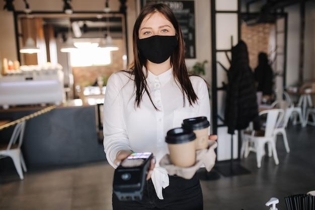 Kassier in gezichtsmasker met creditcardlezer en twee kopjes koffie contactloze betalingen