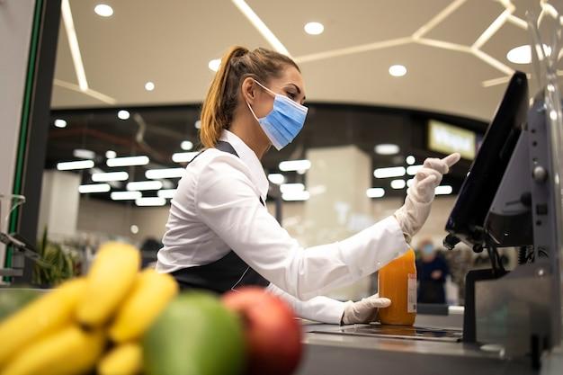 Kassier met beschermend hygiënisch masker en handschoenen aan het werk in de supermarkt en vechtend tegen de coronaviruspandemie.