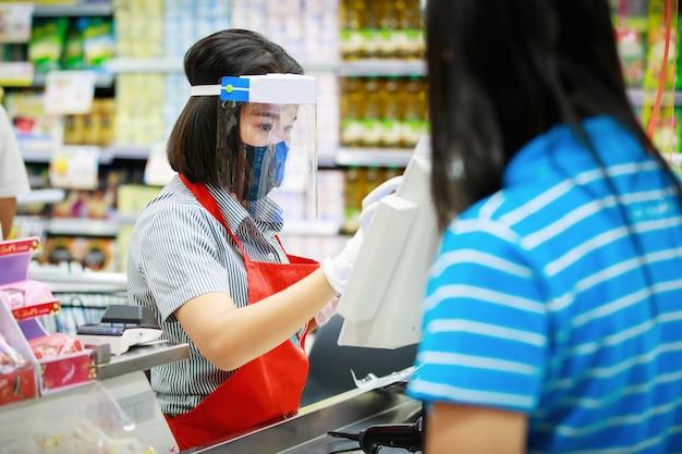 Kassier of supermarktpersoneel in medisch beschermend masker en gezichtsschild dat bij supermarkt werkt.