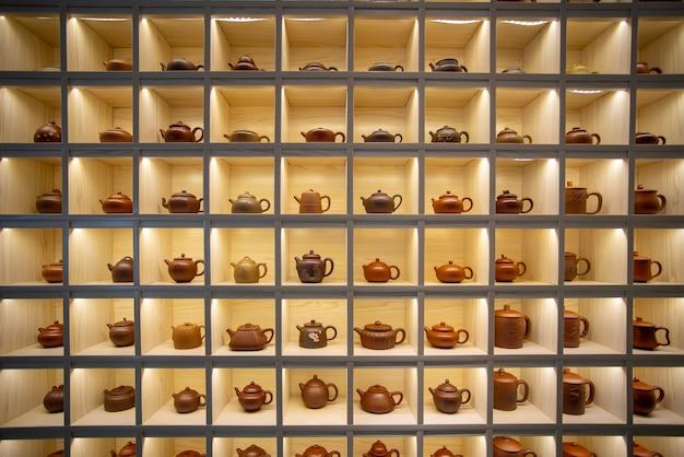 Kast met meerdere roosters gevuld met handgemaakte theepotten