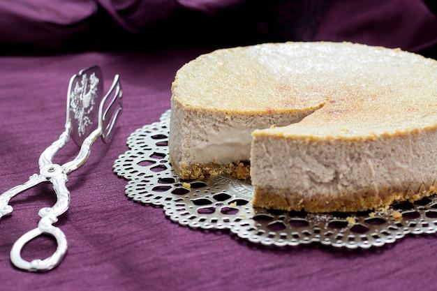 Kastanje-cheesecake-ijs op een zilveren schaal en caketang op paars