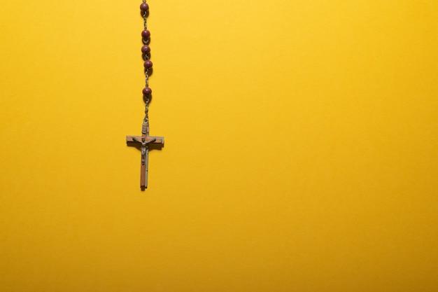 Kastanjebruine kralen rozenkrans met houten kruisbeeld op geel