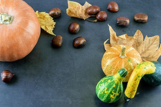 Kastanjes met pompoenen en droge herfstbladeren op donkere tafel