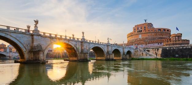 Kasteel van de heilige engel en de heilige engel brug over de rivier de tiber in rome bij zonsondergang.