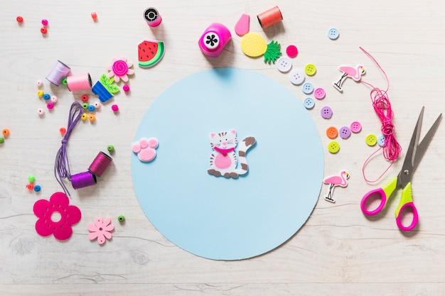 Kat en poot sticker op blauwe circulaire papier met decoratieve items op gestructureerde achtergrond
