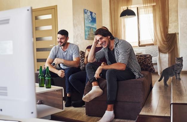 Kat op de tribunes en lachende mensen. opgewonden drie vrienden die samen thuis voetbal kijken op tv.