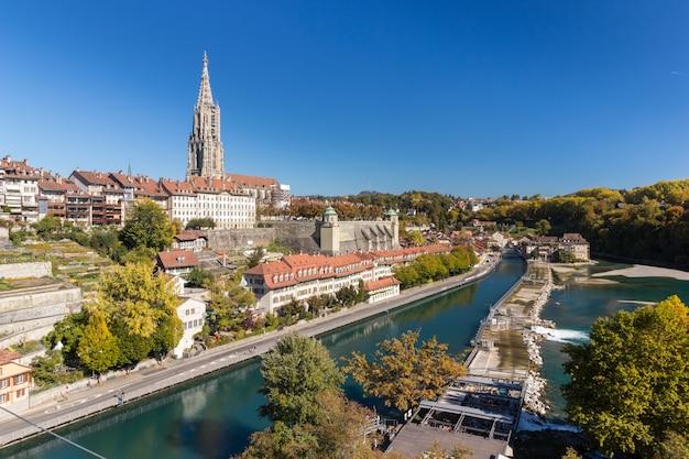 Kathedraal van bern of munster langs de kant van de rivier de aare in zonnige dag, zwitserland