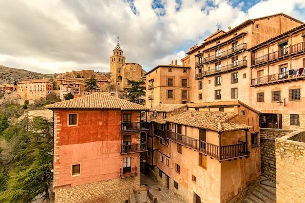 Kathedraal van de stad verheven boven de blauwe hemel met wolken. oude constructie met stenen muren en middeleeuwse architectuur. albarracãn teruel spanje. aragon.