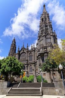 Kathedraal van donkere steen, met een grote toren die tot aan de blauwe lucht oprijst. arucas gran canaria. spanje.