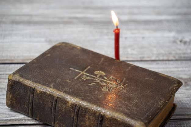 Katholieke bijbel en rode kerk brandende kaars op houten achtergrond