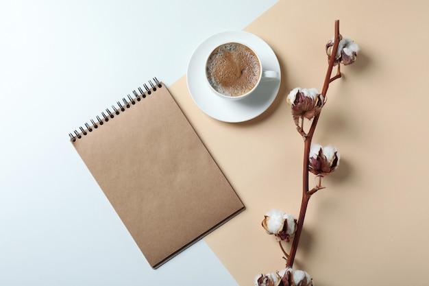 Katoen, notitieboekje en kopje koffie op tweekleurig oppervlak