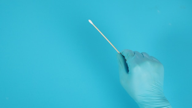 Katoen plakt ter beschikking met blauwe medische handschoenen of latexhandschoen op blauwe achtergrond.