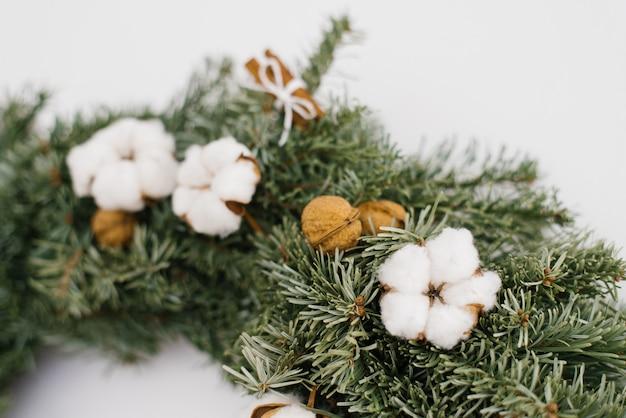 Katoenen bloem en okkernoten in kerstmiskroon, close-up van kroon