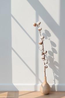 Katoenen bloem in een vaas op een houten vloer