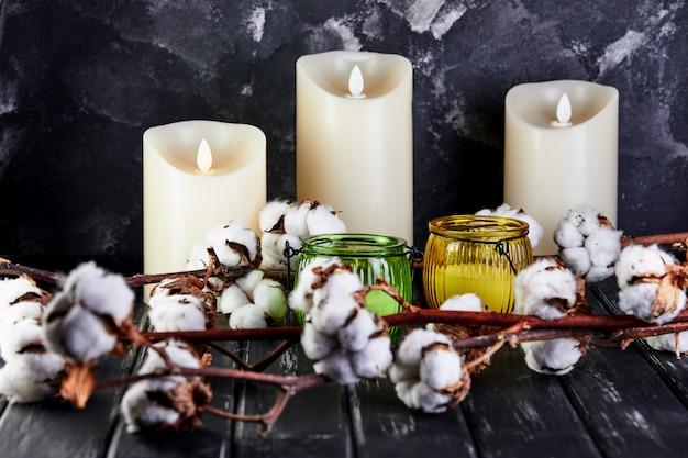 Katoenen bloemen die op een donkere houten achtergrond en kaarsen liggen
