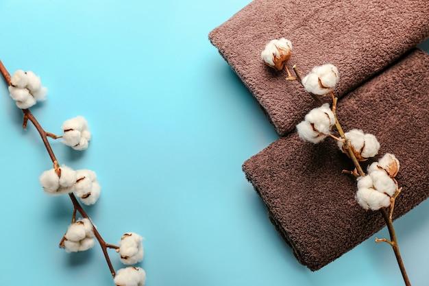 Katoenen bloemen en zachte handdoeken op blauw