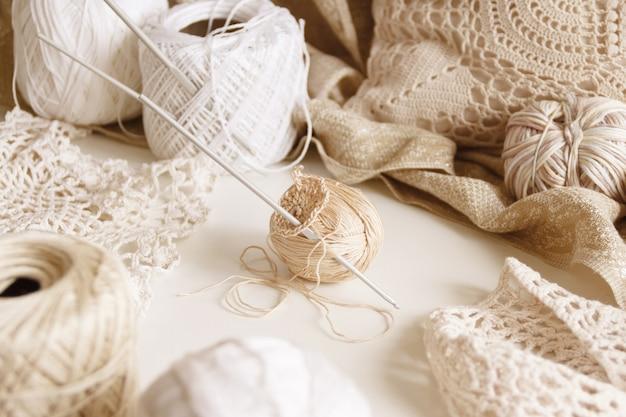 Katoenen draad en haak op een tafel omgeven door beige katoenen ballen en kleedjes