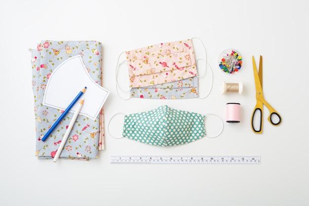Katoenen gezichtsmasker met naaien accessoires op witte achtergrond