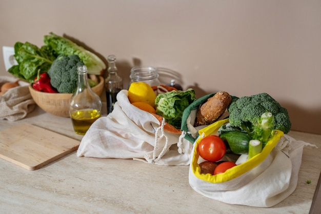 Katoenen herbruikbare tassen met etenswaren en glazen flessen op keukentafel. geen afvalconcept. veganistisch natuurlijk voedsel. biologische lokale gerechten. duurzame levensstijl