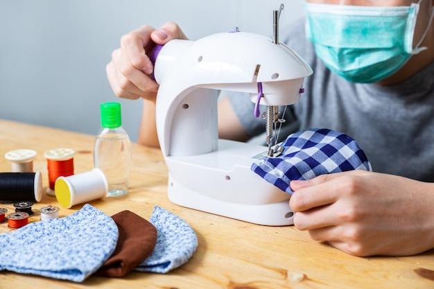 Katoenen het vrouwen naaiende doek gezichtsmasker om thuis tegen het coronavirus te beschermen. zelfgemaakt handwerk beschermend masker tegen covid 19 virus. herbruikbaar gezichtsmasker.