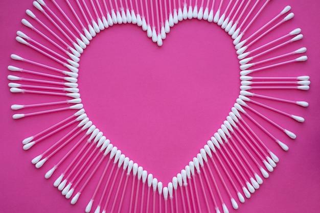 Katoenen knoppen opgemaakt in de vorm van een hart op een roze achtergrond