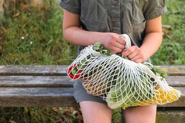 Katoenen koordtas met groenten in de handen van een klein meisje