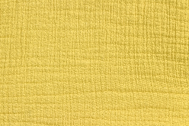 Katoenen mousseline achtergrond in mosterd gele kleur.