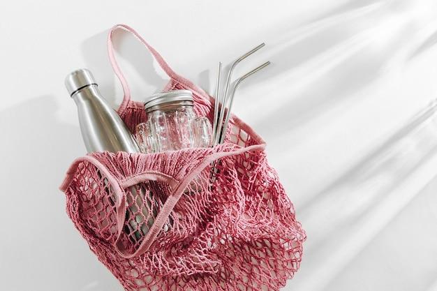 Katoenen nettas met herbruikbare metalen waterfles, glazen pot en rietje. geen afvalconcept