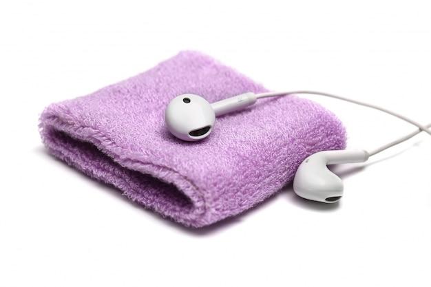 Katoenen polsbandje en oortelefoon op witte achtergrond