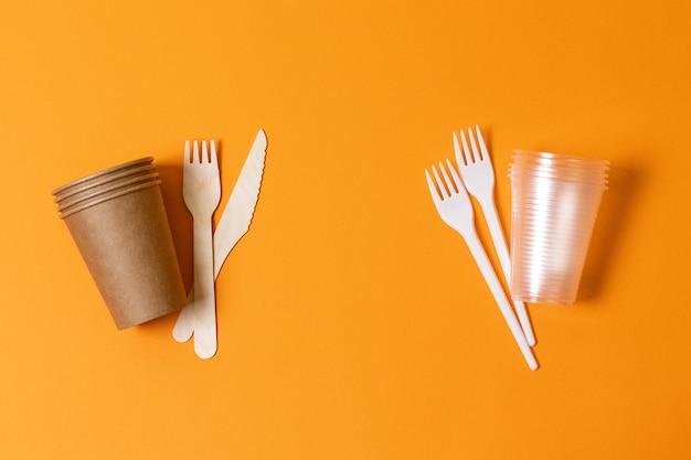 Katoenen tas, houten items en glazen op een oranje achtergrond, ecologische rivaliteit