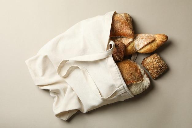 Katoenen tas met bakkerijproducten op grijze achtergrond