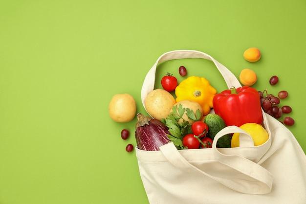 Katoenen tas met groenten en fruit op groene achtergrond