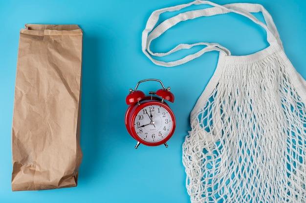Katoenen tassen, nettas. papieren zak. geen afvalconcept. milieuvriendelijk. platliggend met een afbeelding van een rode wekker