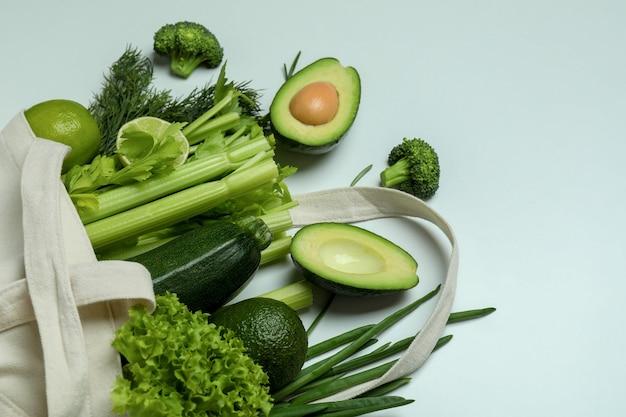Katoenen zak met groene groenten op witte achtergrond