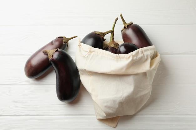 Katoenen zak met verse aubergines op houten