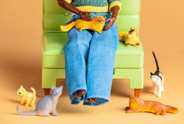 Kattendame met veel katten in een fauteuil. scène met poppen