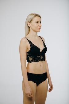 Kaukasisch aantrekkelijk vrouwelijk model poseren in studio, gekleed in zwarte transparante lingerie