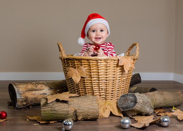 Kaukasisch babymeisje dat met kleren en verfraaide kerstmis glimlacht
