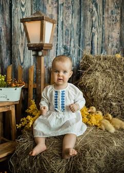 Kaukasisch babymeisje in een witte linnen jurk met borduurwerk zit op een hooiberg met gele eendjes. pasen decoratie