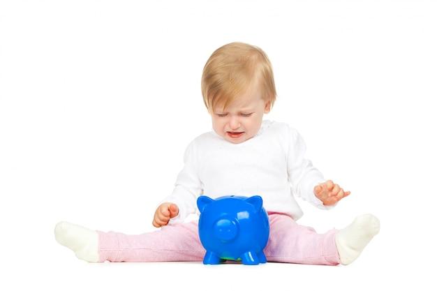 Kaukasisch babymeisje met spaarvarken dat op witte achtergrond wordt geïsoleerd