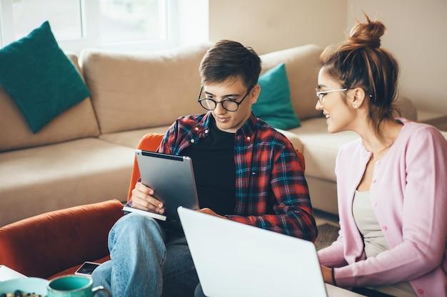 Kaukasisch bedrijfspaar dat bij laptop en tablet werkt tijdens het spreken en het dragen van een bril