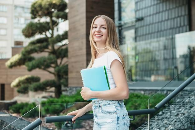 Kaukasisch blond studentenmeisje houdt mappen, notitieboekjes in handen en glimlacht op de achtergrond van het universiteitsgebouw. ruimte kopiëren