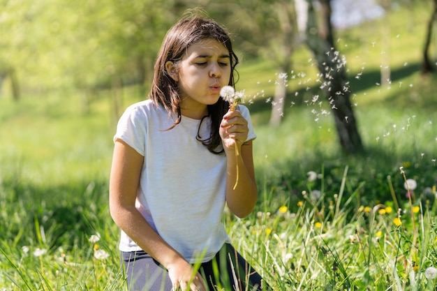 Kaukasisch bruinharig meisje blaast op paardebloem die bloemen blaast in een groen veld vol bloemen