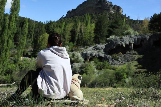 Kaukasisch brunette meisje in het veld met haar puppy