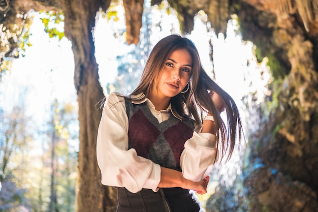 Kaukasisch brunette meisje, schoolmeisje in een zwarte rok en kastanjebruine laarzen in een grot op een herfstmiddag