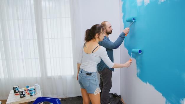 Kaukasisch echtpaar doet een make-over van hun appartement en schildert de muren met een rolborstel. appartement herinrichting en woningbouw tijdens renovatie en verbetering. reparatie en decoreren.