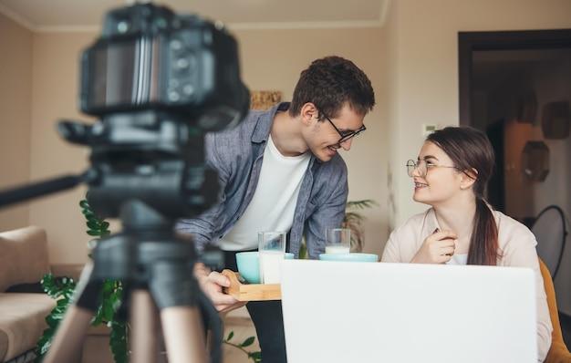 Kaukasisch echtpaar met een bril eet de maaltijd terwijl ze op afstand met laptop en camera werken