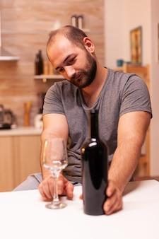 Kaukasisch eenzaam in wanhoop die een fles wijn vasthoudt en bekijkt. ongelukkige persoon ziekte en angst gevoel uitgeput met alcoholisme problemen.