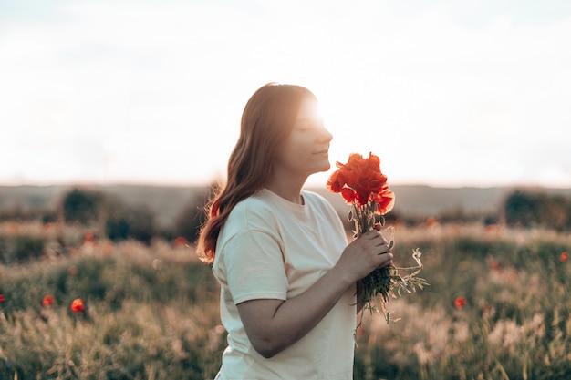 Kaukasisch gelukkig mooi jong meisje met een papaverboeket in haar handen in een zomerveld bij zonsondergang. toerisme, reizen en gezonde levensstijl concept.